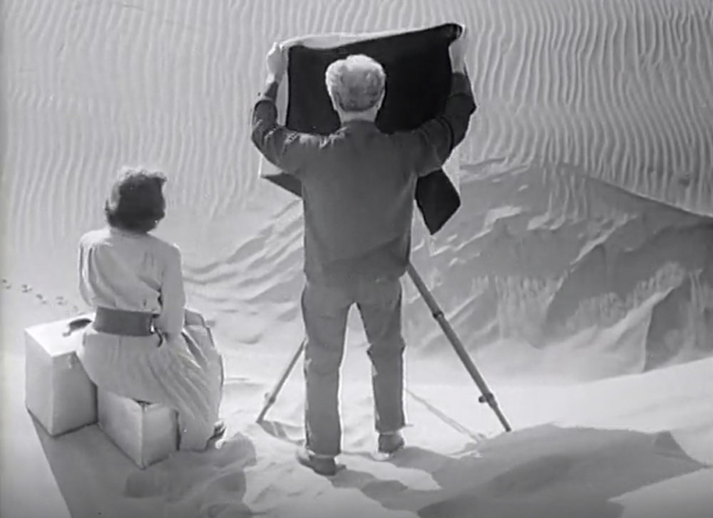 Man stands behind a large format camera raising the focusing cloth.
