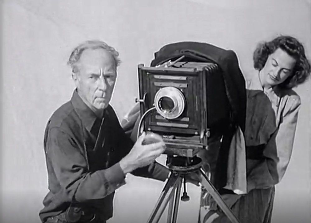 Man and woman stand next to a large format camera