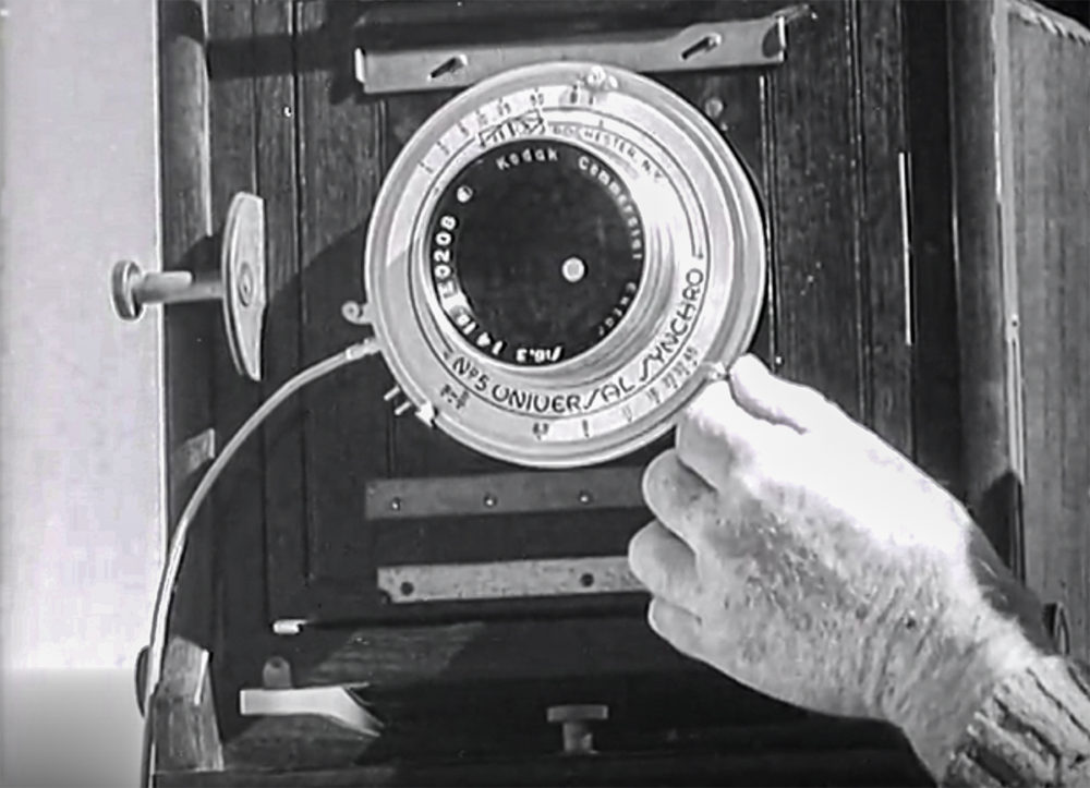 Edward Weston stopping down the lens. Image shows the lens of a large format camera.