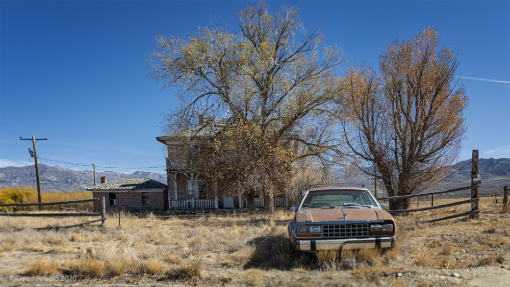 Abandoned car in front of large ranch house.